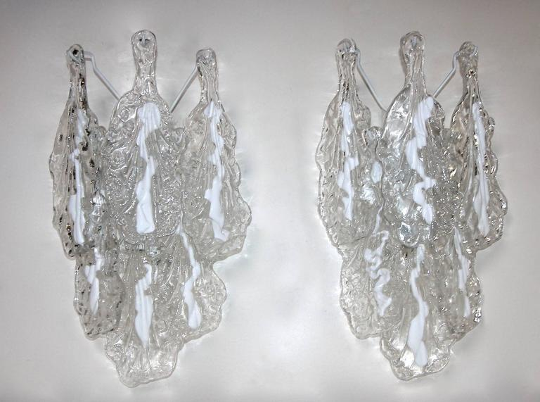 Pair of Mazzega Italian wall sconces with handblown textured clear and white glass leaf shaped petals suspended on white painted metal back plates. Newly wired for the US, each sconce uses two candelabra base bulbs.