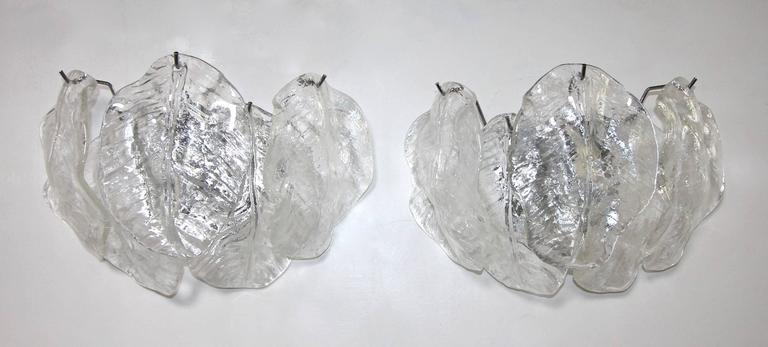 Two Pairs (4 total) of Italian Murano clear textured glass leaf wall sconces with nickel plated steel backplates, attributed to Mazzega. Rewired for US, each fixture uses two candelabra a base  bulbs.  Measures: 13.5