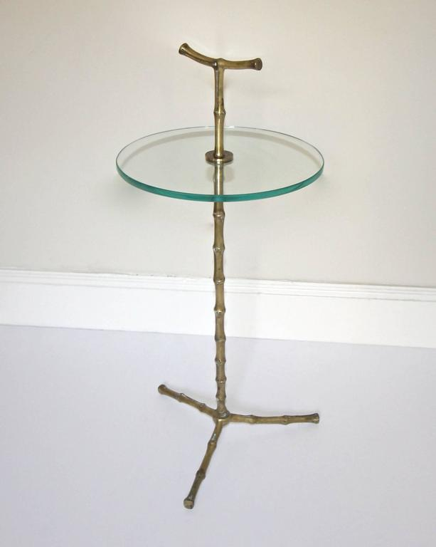 Maison Baguès faux-bamboo bronze or brass side table with a circular glass top and tripod base.