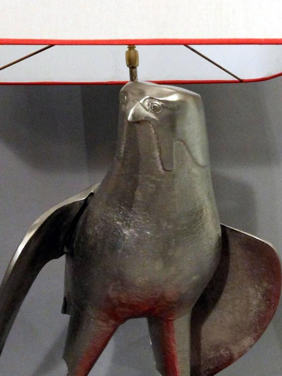 Rare 1970s table lamp constituted by an hawk in nickel-plated solid bronze on a wooden red lacquered base. Numbered 10. New lampshade in cloth grey silvery lined with a red bias. The lamp is very heavy.  Dimensions without lampshade: Height 60