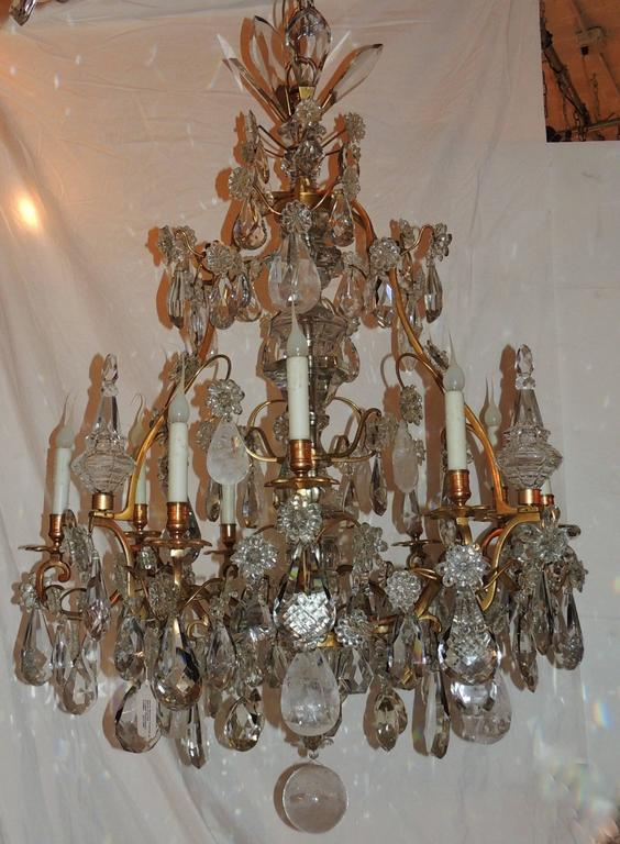"""This beautiful nine-light chandelier is layered with wonderful scrolling doré bronze arms, multifaceted and textured crystal pendants and highlighted by rock crystal pendants and crystal obelisk.  Measures: 52"""" H x 32"""" W."""