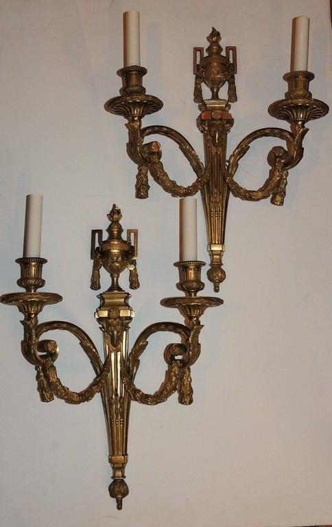 """A wonderful Large pair of beautifully etched doré bronze two-arm sconces with filigree draping and swags with fluting detail and decor around the bobeches and a ram's head center medallion of the sconces In the Louis XVI manner.  Measures: 20"""""""