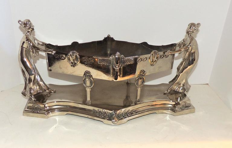 A wonderful silver plated Art Deco centerpiece with two female figures supporting the diamond shape centerpiece with removable insert. Decorated with draping, wreaths and filigree detail.  Measures: 18