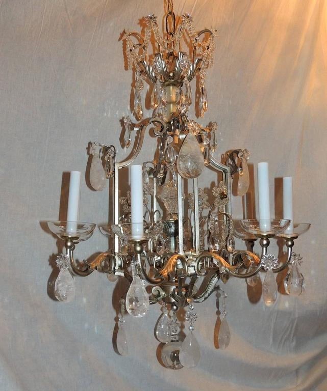 This is a fabulous and unusual pagoda form chandelier that has a beautiful crown with draped crystals and beading. Each of the eight scrolled arms have a crystal flower from which hangs a rock crystal. The chandelier is finished with a rock crystal