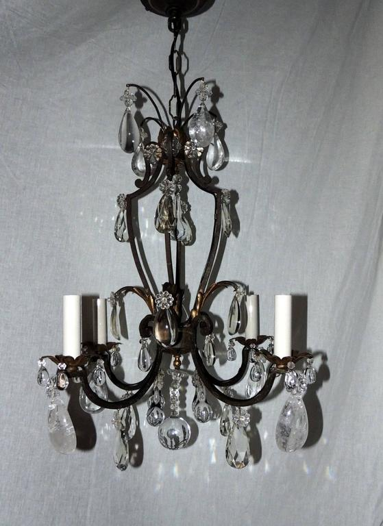 A wonderful French gilt rock crystal four-light Bagues Jansen Petit light fixture, perfect for the smaller space, this wrought iron chandelier with gilt leaves accenting the center and bobeches. In the manner of Bagues & Jansen  Measures: 22