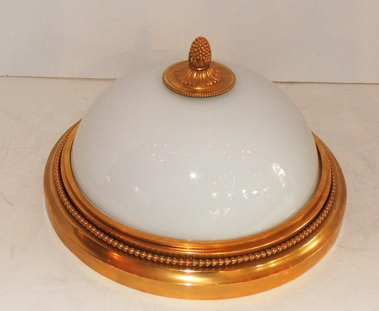 A wonderful Sherle Wagner doré bronze and white dome glass flush mount light fixture. This beautiful fixture is set with two candelabra bulbs taking a maximum of 60 watts per socket. In excellent condition, and come ready to install and