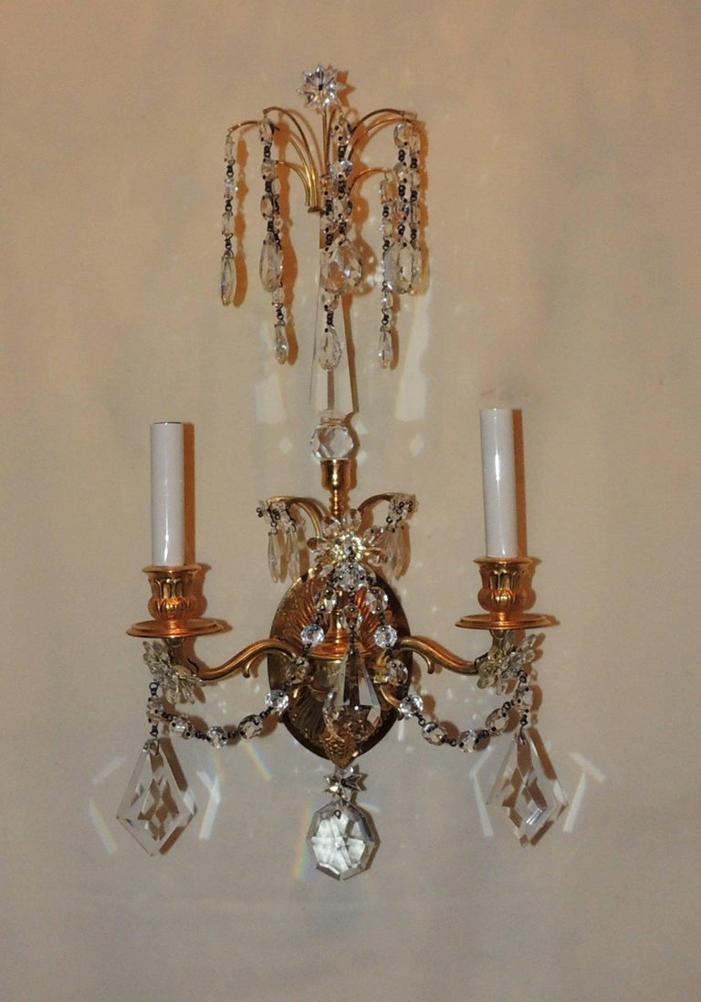 A wonderful pair of doré bronze neoclassical two-arm draped crystal sconces with draped crystal and