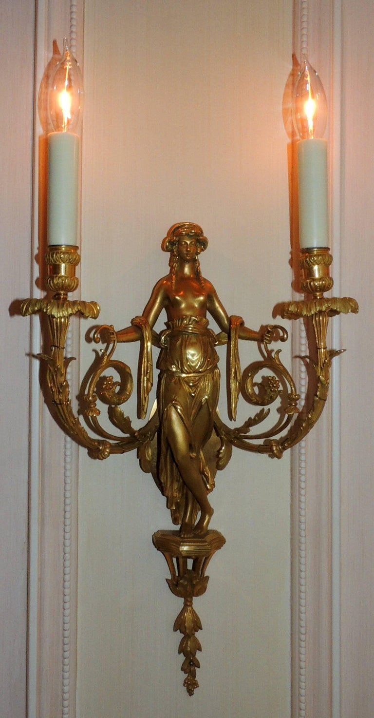 A wonderful pair of French doré bronze female/maiden sconces with floral garlands and swags in the regency decor attributed to Francois Linke.