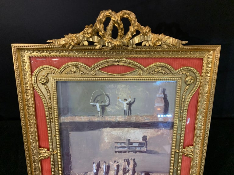 A wonderful French gilt bronze and salmon / pink enamel bow top picture frame.