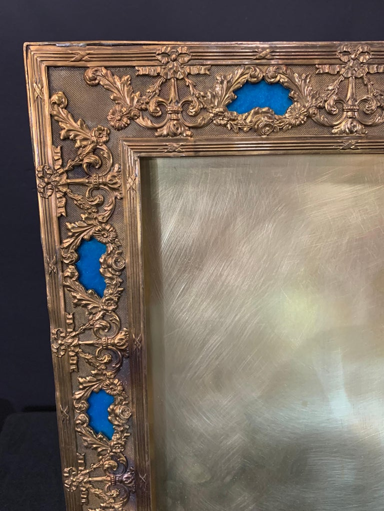 A wonderful french large blue enamel inset and bronze picture frame with bows and swags.