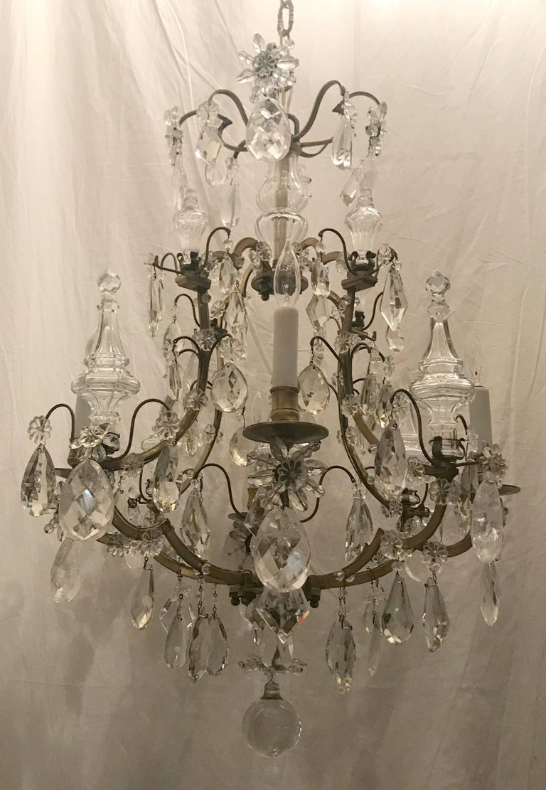 A wonderful French gilt bronze and mixed rock crystal chandelier in the manner of Bagues & Jansen in the midcentury bird cage form finished with four large and four small crystal spike / obelisks and alternating the four candelabra lights with glass