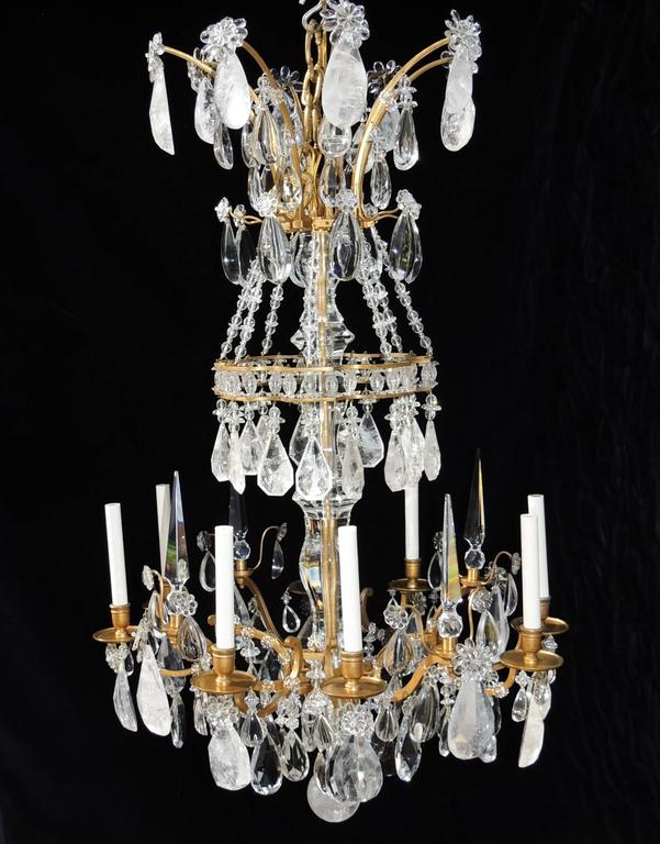 This majestic eight light Dore Bronze Chandelier has multi layers of clear and rock crystal encircling each section. There is a large crystal shaft in the center and wonderful spires accenting the candle lights.  