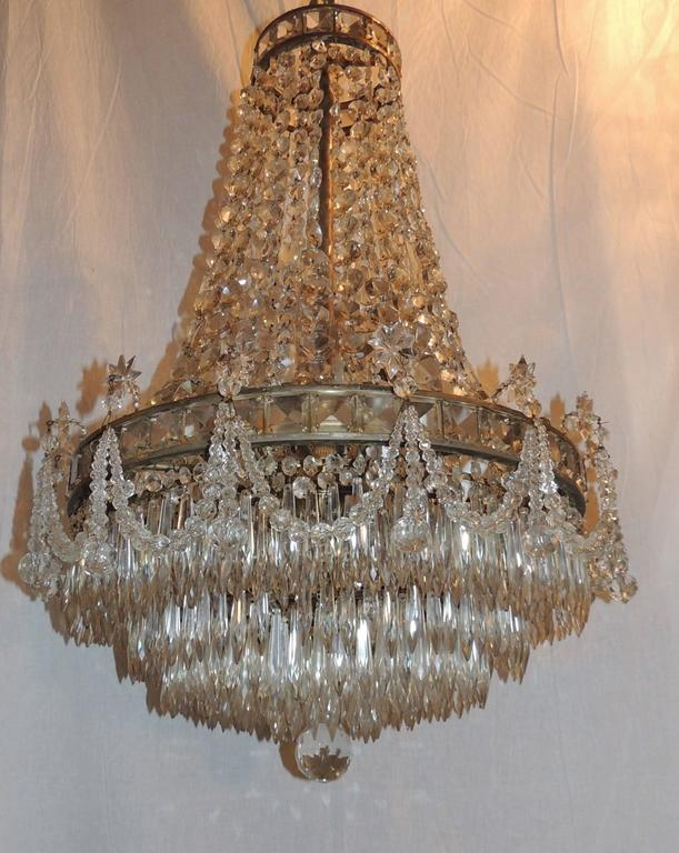 Large Empire ten-light ballroom style chandelier with nine layers of prism crystals at the bottom and finished with beautiful crystal prisms draped and accented with prism stars and a prism cut crystal ball. Finished in antique silver over bronze