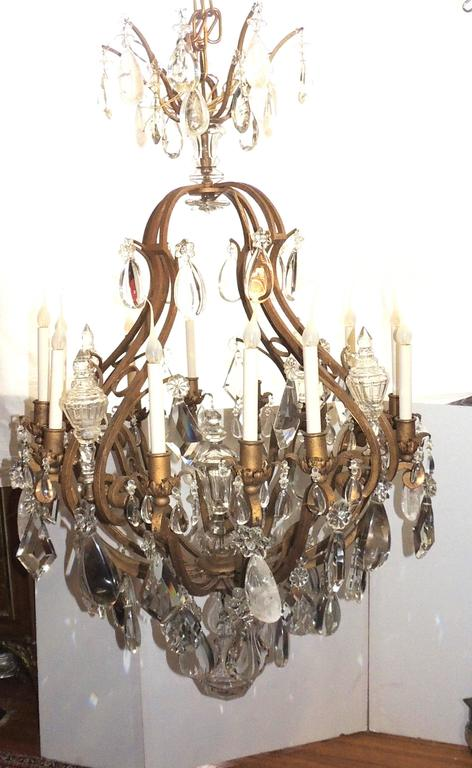 """This wonderful Very Large 1920s gilt iron French cage chandelier has twelve lights with an assortment of flat, prism, faceted and rock crystals finished with a large beveled ball at the bottom. In the Bagues Manner  Measures: 55"""" H x 33"""""""