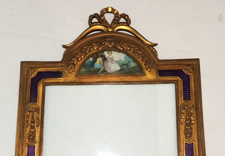 A wonderful and rare French ormolu bronze and purple enamel picture frame with a miniature on the top with bows and tassels. 