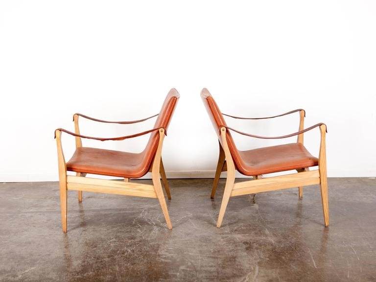 Rare pair of Ebbe & Karen Clemmensen. Safari chairs with original brown leather and an ash frame. Model 4305, designed in 1958, Danish, produced by Fritz Hansen. Some wear and a few small tears in one of the chairs which has been repaired.