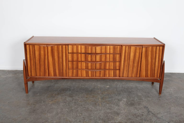 Four-door, four-drawer sideboard made in tola with floating side legs by Elliots of Newbury (EON) of the UK. Newly refinished.