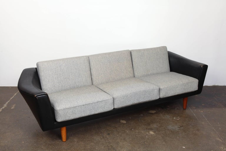 Danish Mid-Century Modern black leather tuxedo style sofa with round tapered teak legs and loose back/seat cushions designed by Illum Wikkelso. Sofa has original leather and original grey wool fabric cushions.