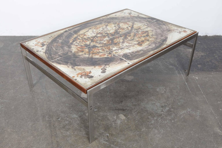 Danish 1970s coffee table with a ceramic tiled top, metal legs and rosewood accents. Designed by Birte Howard. Table has a beautiful off-white, grey/black and brown swirl design to it. All tiles are intact and the table is in very nice condition,