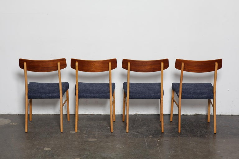 Set of 4 teak bent back Danish dining chairs by Farstrup with beech legs. Newly refinished in a natural teak oil and reupholstered in a navy woven fabric.