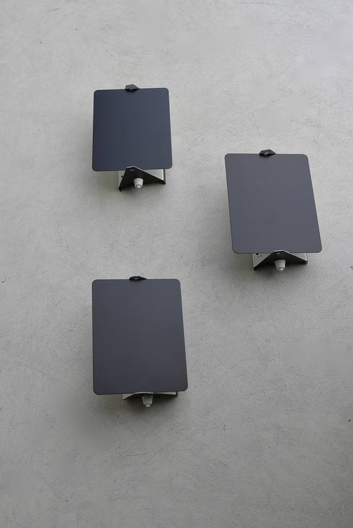 Black and white enameled pivoting wall lights by Charlotte Perriand for Les Arcs Ski Resort. Lamps can be arranged in many configurations to accommodate all living environments.