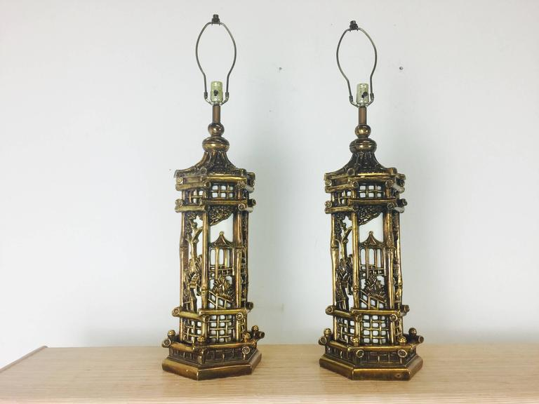 """Pair of chinoiserie gold lamps the style of James Mont. These lamps not only light from the top but also inside the body. There is wear due to age of pieces, circa 1950s.  Dimensions: 10"""" diameter x 37"""" top (top of harp)  Shades not"""