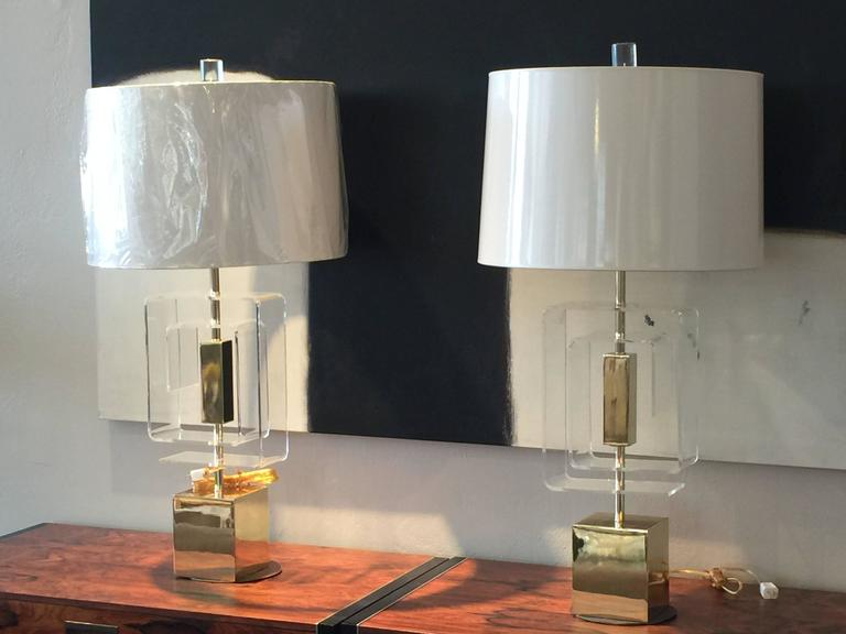 Pair of Lucite and brass lamps by Laurel. There is a minor imperfection on top of one of the bases. Lamps have recently been newly wired.