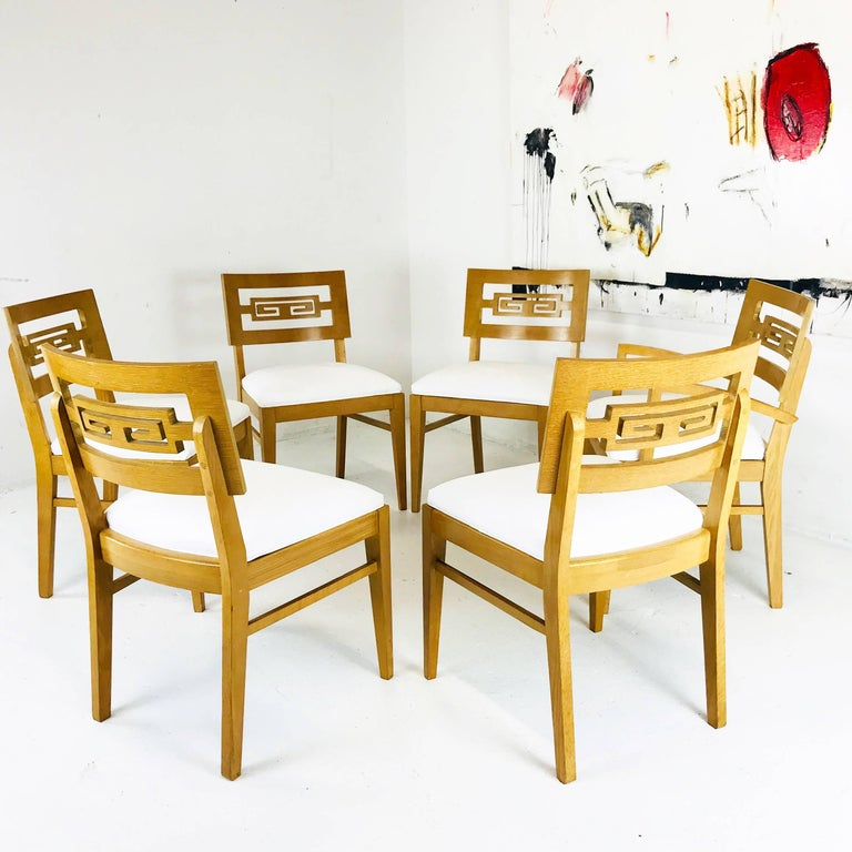 Set of six Greek key dining chairs. There are five side chairs and one armchair. Seat cushions were recently upholstered. Wood finish is in good vintage condition with signs of wear due to age and use, circa 1960s  Dimensions: 22.5