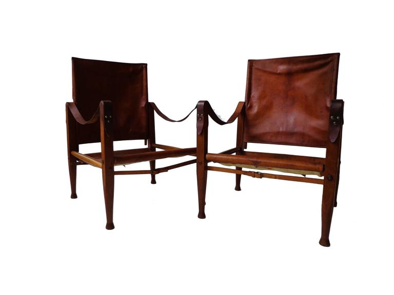 """Offerd by Zitzo, Amsterdam: A pair of stained ash """"Safari chairs"""". Seat, back, armrests in original patinated cognac niger leather and brass details. Designed 1933. Signed with early applied manufacturer's label to each"""