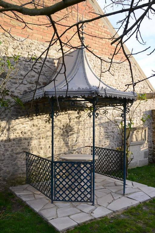 Dated mid-19th century, Napoleon III iron and zinc summer house to be applied to a wall and resting on four cast iron pillars. Its pagoda-shaped roof topped with a cluster of spikes is under the Japanese influence. This new trend of Japonisme is