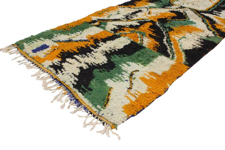 This hand-knotted wool vintage Berber Moroccan rug features an all-over contemporary abstract design. Rendered in green, orange, black and ivory-beige with a hint of blue and brown. With its contemporary and abstract design, this Berber Moroccan rug