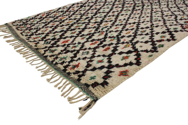 Add a Boho Chic vibe to your home with this vintage Berber Moroccan rug featuring a modern tribal style. Made in Azilal from the High Atlas Mountains of Morocco. A vanilla-ivory field with black lines creates an overall lozenge pattern framing