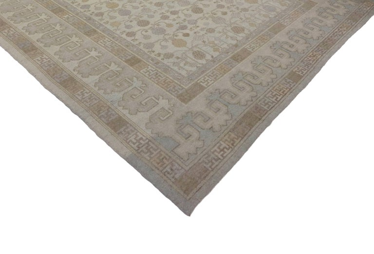 Representing a stylish union of traditional and modern, this sophisticated chic Khotan style rug features a traditional all-over pattern of pomegranates with a modern aesthetic. The warm beige and pomegranates create a mesmerizing effect when placed