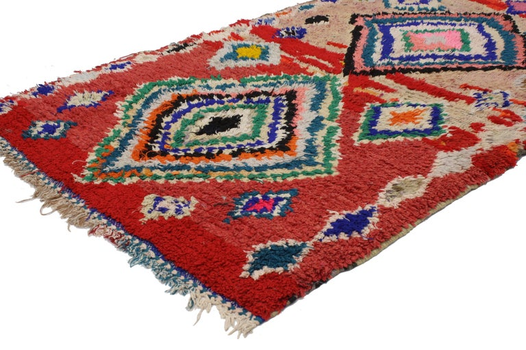 With the dramatic red color and modern tribal style, this vintage Berber Moroccan rug is not for the timid. Rendered in red, hot pink, blue, teal, aqua, green, powder blue, black, gray, lavender with colorful accents. Features two large diamonds