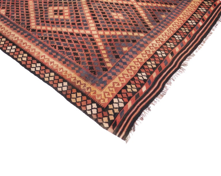 Boasting a stunning tribal design and modern style, this vintage Afghan Kilim rug shows its age beautifully. From variegated shades of rust, slate blue and dark brown to vibrant apricot, beige and charcoal gray, the colors combined with the