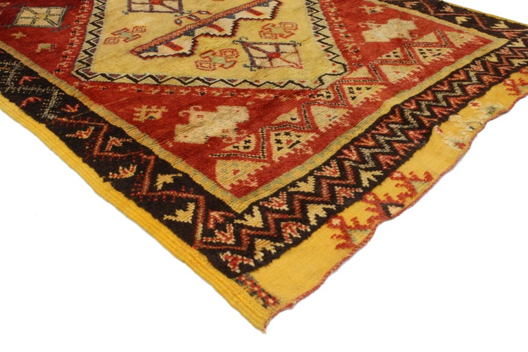Impeccably woven from hand-knotted wool and displaying a modern tribal style, this vintage Berber Moroccan rug features three medallions surrounded by symbolic Berber motifs in an abrashed red field. Blending the graphic appeal and folk art warmth