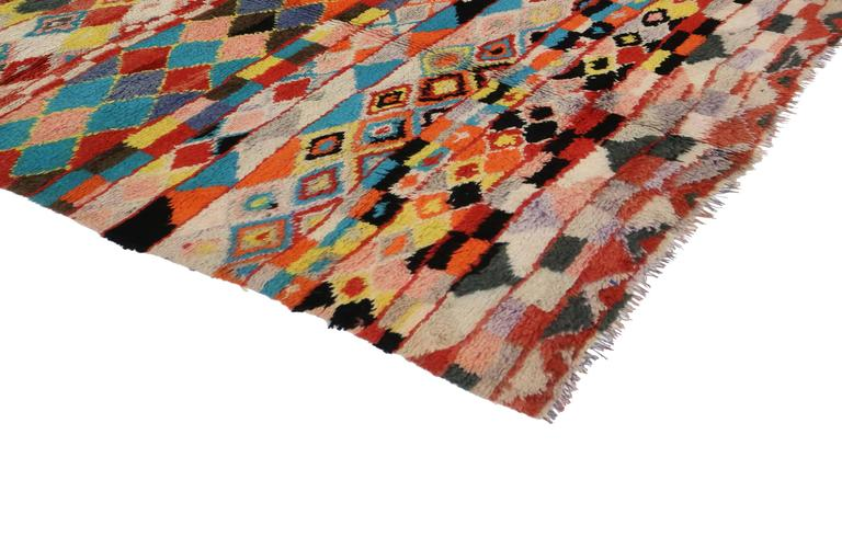 This vibrant wool rug is from the Azilal region of the High Atlas Mountains of Morocco. Featuring bold colors and incomparable textures in a variety of colors, this vintage Berber Moroccan rug is an amazing Primitive abstract work of art and well