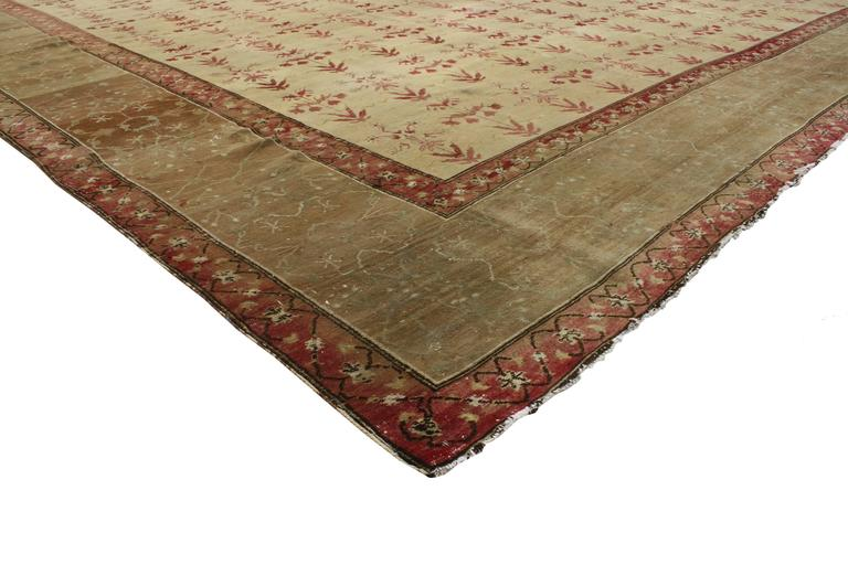 The repetitive pattern in this antique Indian Agra rug synthesizes beautifully with modern architecture and modern traditional style. Impeccably woven by Indian artisans, this antique Agra rug relies on its time-softened colors to relax its