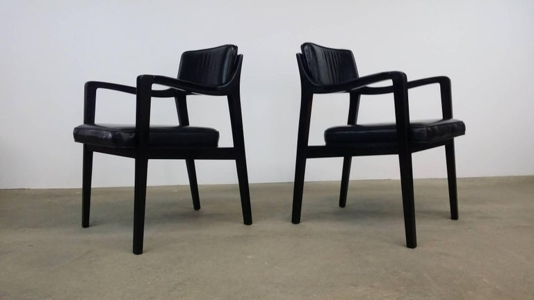 Pair of Dunbar chairs in mahogany and black leather, designed by Edward Wormley, circa 1966. Professionally refinished in a very dark, almost ebony finish. Original black leather in excellent condition.
