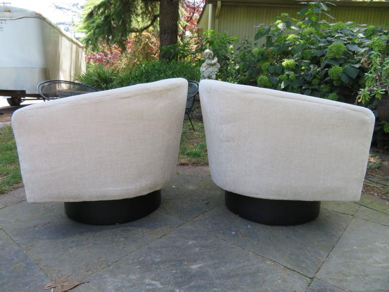 Fantastic pair of Milo Baughman tall swivel base barrel back lounge chairs. The unique tall swivel bases have an ebonized finish and look very nice. This pair retains their original fabric and will need new upholstery.