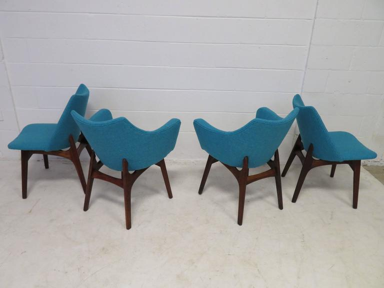 Fabulous set of four Adrian Pearsall sculptural walnut dining chairs. The set consists of two armchairs and two side chairs. They have been reupholstered in a wonderful period appropriate nubby woven fabric in a cool turquoise. We have many Adrian