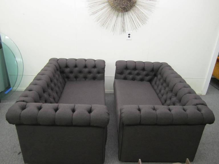 Stylish pair of Harvey Probber style Chesterfield loveseat sofas. Both have newer charcoal black woven fabric in very nice condition. Castors on the underside make moving them around a snap. This pair is ready to slip right into your Mid-Century