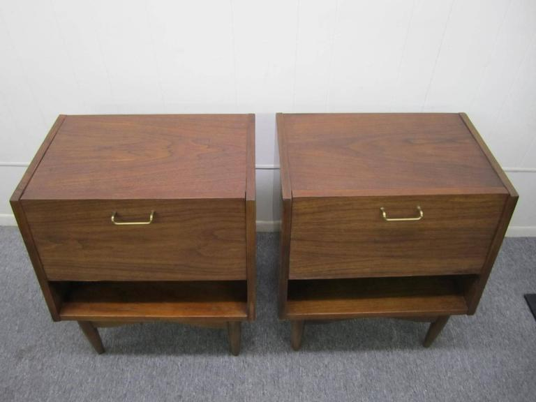 Great looking pair of American of Martinsville walnut nightstands. These stylish nightstands have a great flip down door opening to reveal a nice open space with on small drawer. The inside of the door has a durable Formica finish and works great