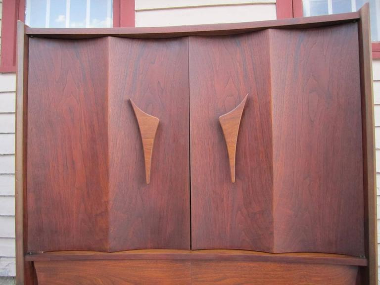 Bowed front sculptural walnut tall dresser. This gorgeous piece has beautifully carved double curved doors that open to reveal and nice bank of drawers. Just look at the two large drawers down below how neat they are constructed. This piece is in
