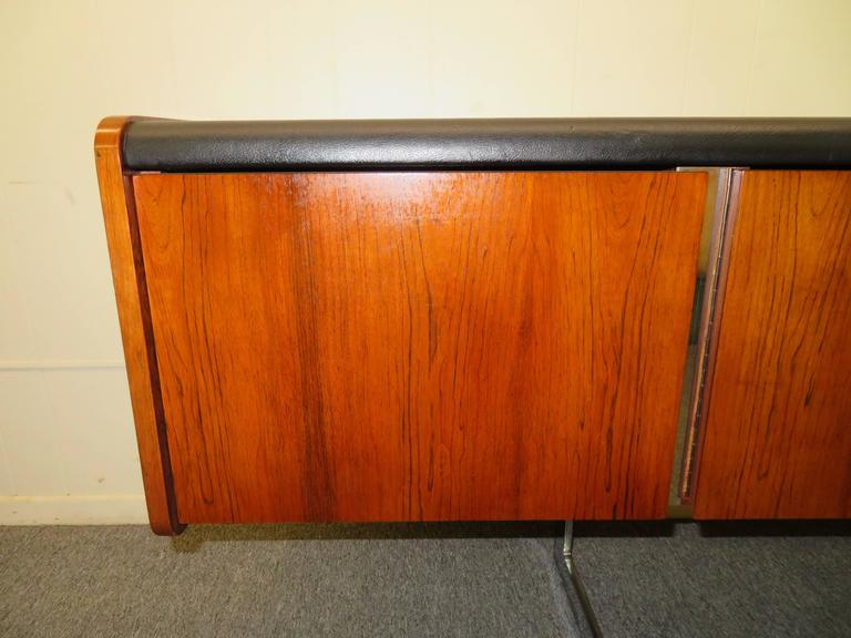 This Ste-Marie and Laurent sideboard has beautiful rosewood grain and a black faux leather top. This Mid-Century credenza floats on a modern chrome cantilever base and is finished on all sides. Left drawer holds hanging files and would be perfect