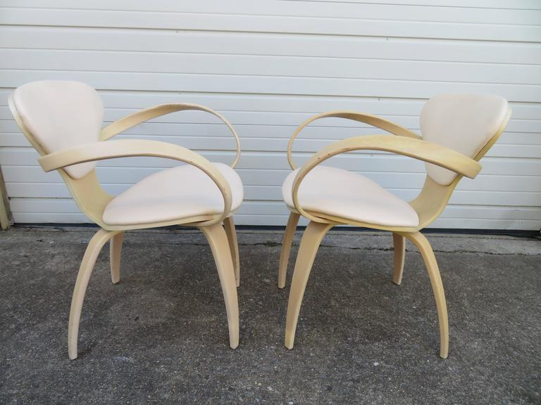 Lovely pair of labelled Norman Cherner Plycraft pretzel armchairs. This pair has a pickled white finish and bone colored faux leather in nice vintage condition.