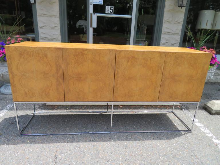 Sideboard by Milo Baughman for Thayer Coggin.  Dramatic burl olive wood case supported by chromed steel base. Cream lacquer interior. This piece is in excellent vintage condition with only very minor signs of wear. You will be well pleased with the
