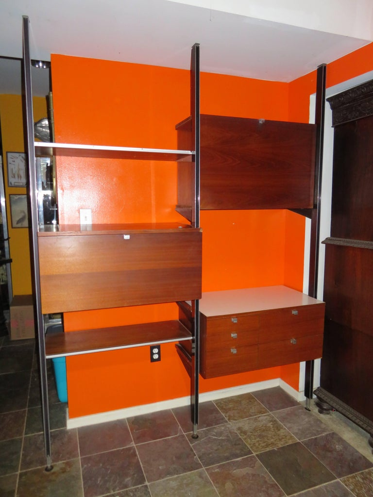 Original signed two bay comprehensive storage system CSS by George Nelson for Herman Miller. This system consists of three spring loaded aluminium poles, three cabinets and two shelves. This system can be arranged in multiple ways and also can be