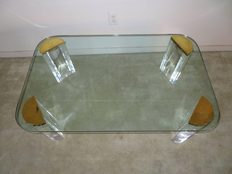 Midcentury chunky Lucite and brass coffee table. This unusual table is in very nice vintage condition and makes a stunning statement-like a piece of jewelry.