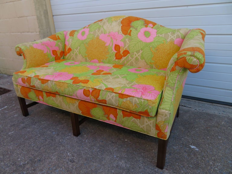Wonderful flowered linen Chippendale style camelback loveseat sofa with mahogany legs.  We love the original bright flowered linen used on this sofa-gives it great vintage appeal.